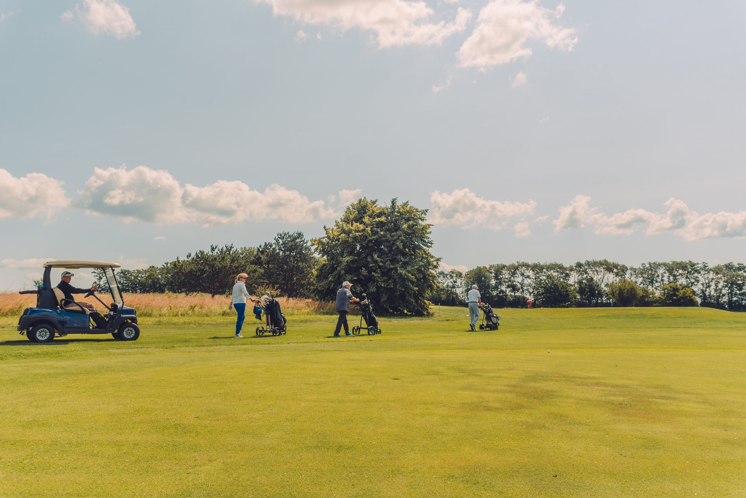 Golfcart und Golfspieler am Weg zur nächsten Bahn.