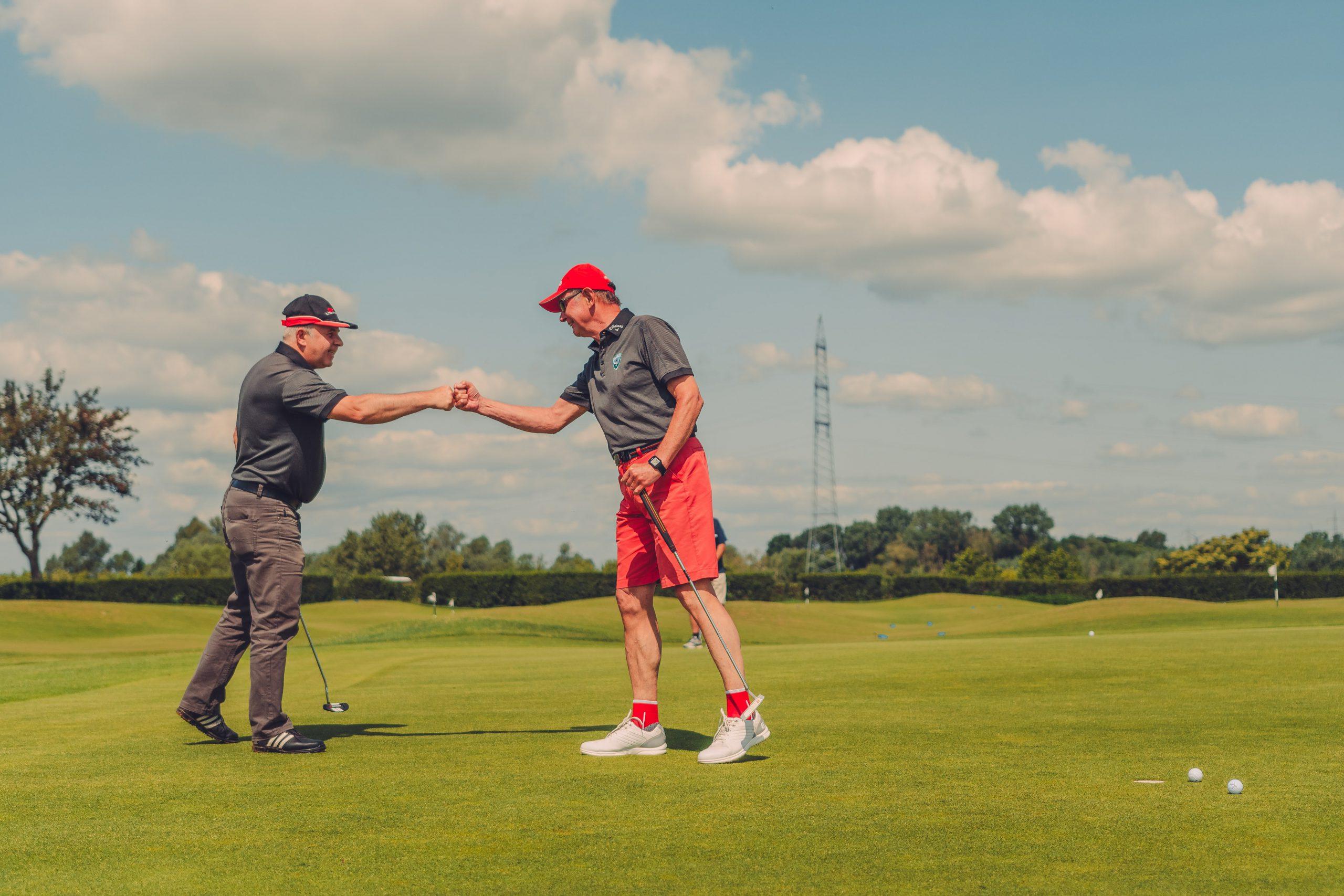Zwei Golfspieler freuen sich über einen Erfolg.